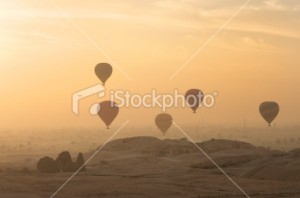 17270107-17270107-hot-air-balloons-float-along-sunrise-horizon